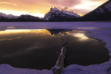 Scenic view of snowcapped mountains and lake at sunset