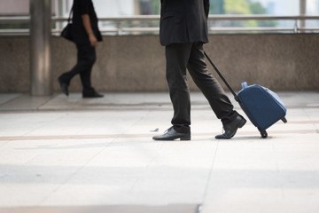 businessman hand holding luggage in area train station