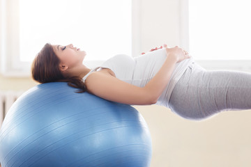 Portrait of a beautiful young pregnant woman executing exercises with fitball