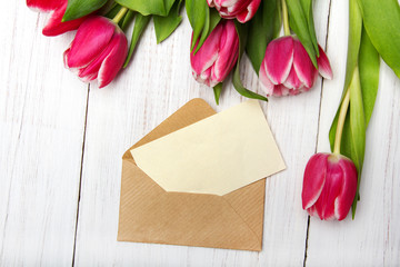 Tulip bouquet and envelope on white wooden background, copy space