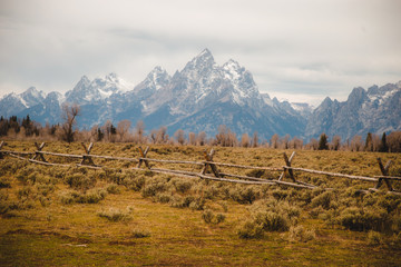 Wooden fence through rural setting, mountain range in background