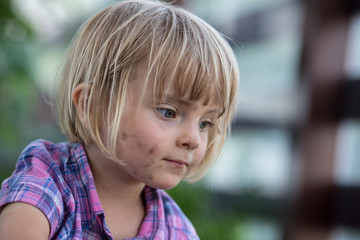 young baby caucasian blonde girl with dirty face portrait at her family urban vegetable garden