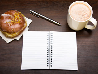Open notebook, tasty donut and cup of coffee on brown wooden table, copy space.