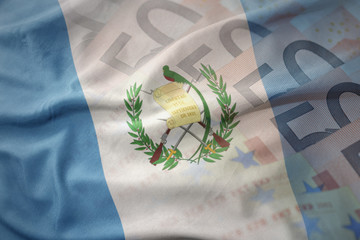 colorful waving national flag of guatemala on a euro money banknotes background. finance concept