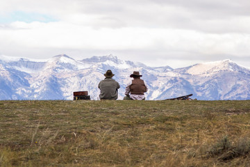 Two people sitting on mountainside, looking at view, rear view