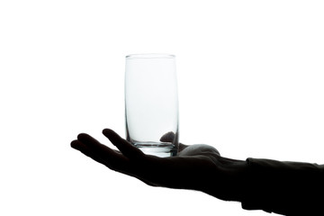 Man's hand with a glass without water to drink - silhouette
