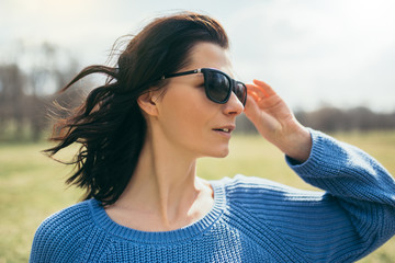 Portrait of a young brunette happy woman in sunglasses at the park. Caucasian happy attractive female outdoors in the spring on sunshine day, looking away. Pretty girl with windy hair, freedom view.