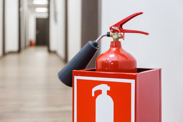 Fire extinguisher in white corridor of the business center