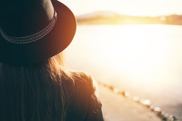 Rear view of hipster woman with hat at sunset