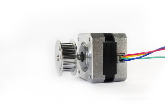 Electric stepper motor with a shiny metal timing pulley mounted to the shaft is laying down on its side ready to be used in a mechanical engineering or hobby robotics project.