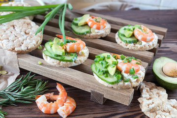 Rice cakes with sliced avocado cucumber shrimp and cream cheese.  Fresh parsley and rosemary. Vegetarian, vegan concept. Shallow depth of field. Coloring and processing photo.