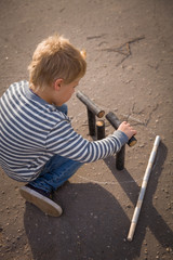 Cute blond kid boy in a striped sweatshirt playing skittles in the street. Russian game skittles. Wooden skittles. Outdoor activites with children. Child playing in the sun.