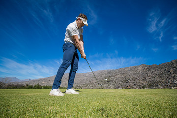 Wide angle view of a golfer teeing off from a golf tee on a bright sunny day on a golf course in south africa.