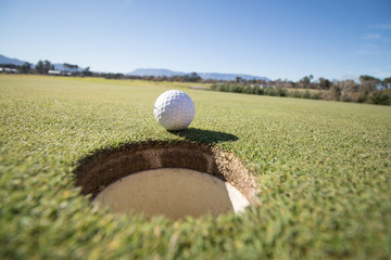 Close up wide angle view of a golfer about to put a ball into the hole on a green on a golf course in South Africa