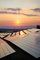 Sunset over solar power plant in countryside. View from above.