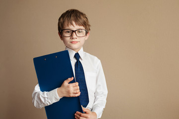 Smart boy in elegant suit and glasses sitting on a Chesterfield sofa with a Tablet paper. Educational concept. Children's fashion. Vintage style. Copy space.
