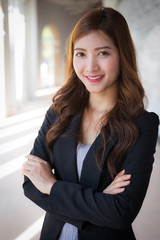 Businesswoman standing crossed arms with smiling face and blurred background