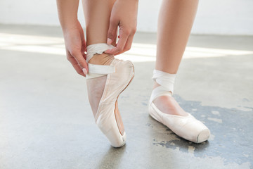 Beautiful legs ballerina in pointe in grey background