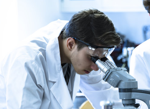 Focused male science student looking in a microscope