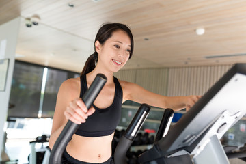 Sport Woman training on Elliptical machine