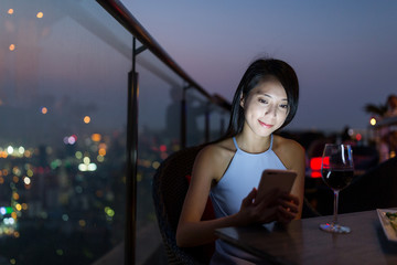 Woman use of mobile phone in outdoor bar at night
