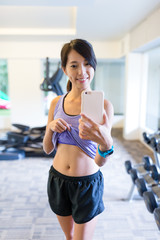 Sport woman with smartphone taking mirror selfie in gym