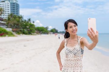 Woman taking selfie by smart phone in the beach