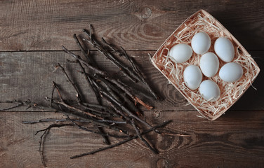 Eggs in a basket with brushwood on a wooden table. Top view. Flat lay.