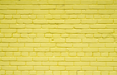 Old brick brick wall painted with yellow paint for textures or backgrounds
