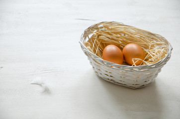 White basket with two beige eggs