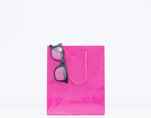 cool black glasses on the pink shopping bag on the wonderful white background