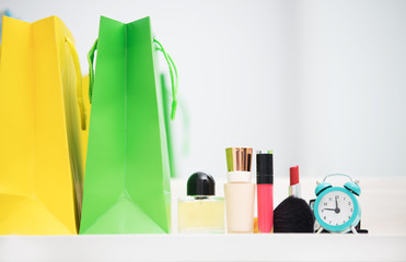 cute shopping bags, make up set and alarm clock on the wonderful mirror background