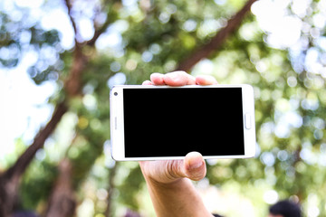 hand holding a smart phone on blurred graduate background