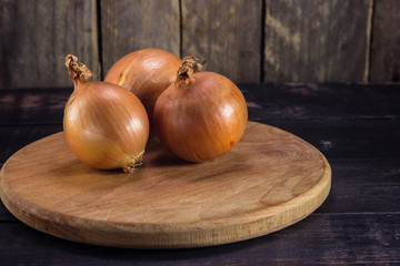Fresh onions on a cutting board on the kitchen table