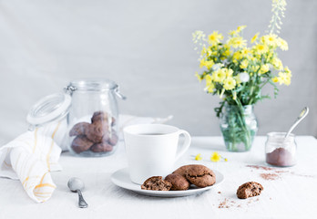 Still life. Chocolate cookies with cup of tea and yellow flowers. Breakfast at sunny spring or summer morning.