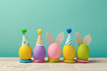 Easter holiday concept with cute handmade eggs, bunny ears and party hats