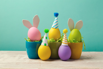 Easter holiday concept with cute handmade eggs in coffee cups, bunny ears and party hats on wooden table