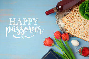 Jewish holiday Passover Pesah greeting card with seder plate, matzoh and tulip flowers on wooden background