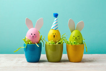 Easter holiday concept with cute handmade eggs, bunny, chicks and party hats in cup on wooden table