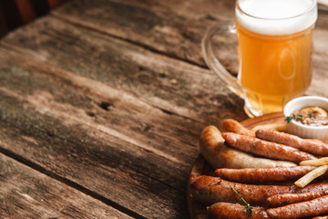 Mug of light beer and plate with various grilled sausages, close up view. German bar menu photo. Wooden background with copy space.