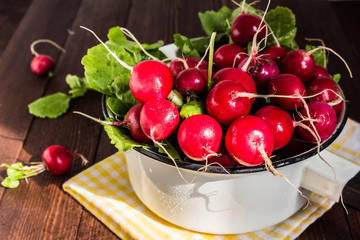 Red radishes in bowl on wooden table