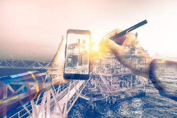 Double exposure of refinery oil and gas background, and businessman on hipster shirt use mobile phone