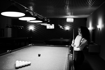 Young curly girl posed near billiard table. Sexy model at black mini mini skirt play russian snooker. Play game and fun concept.