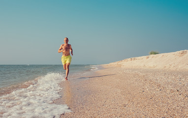 Man runs on the sea surf line