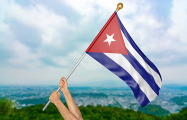 Young man's hands proudly waving the Cuba national flag in the sky, part 3D rendering
