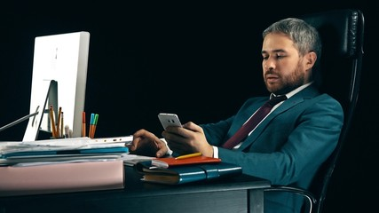 Handsome bearded businessman working on the computer and using his smartphone. Black background