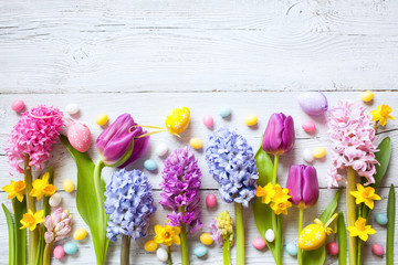 Spring easter wooden background with eggs, candy and flowers