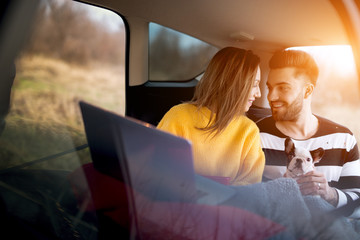 Countryside view. Beautiful couple travelling by car, looking happy.