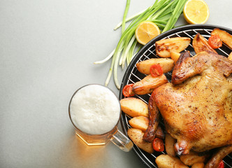 Grilled beer can chicken with vegetables on grey background