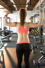 Back view of a sporty woman posing in gym.